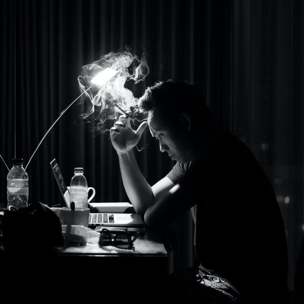 Homme qui fume devant son ordinateur